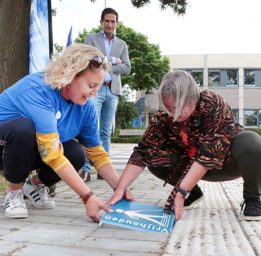 Afbeelding Een cliënt en medewerker van Visio leggen de stoeptegel in Huizen