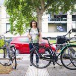 Vrouw loopt op geleidelijn tegen een fiets