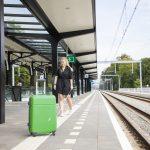 Vrouw loopt op geleidelijn op perron tegen een koffer