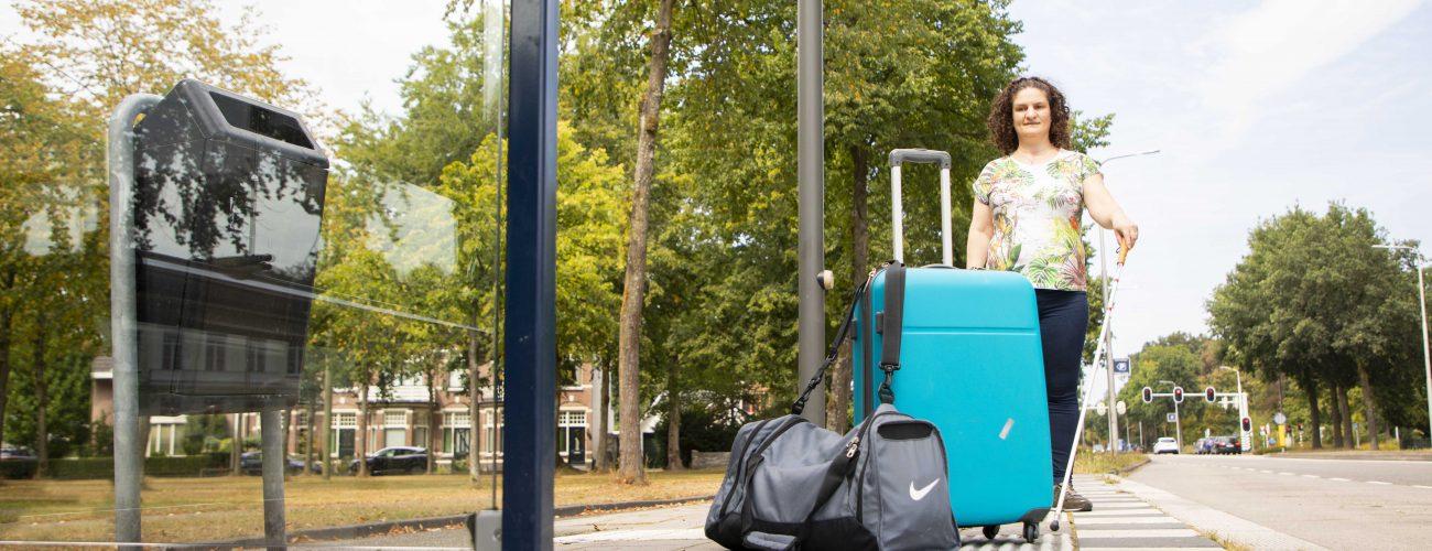 Vrouw loopt op de geleidelijn tegen een tas en een koffer aan