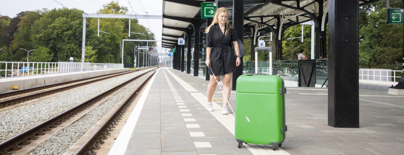 Anouk loopt op de geleidelijn op een perron, op de lijn staat een grote koffer