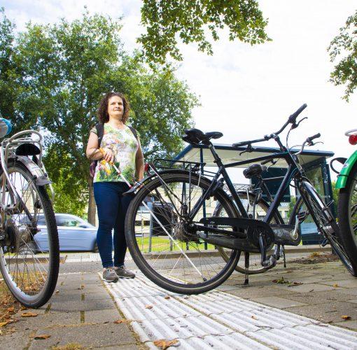 Nursel loopt op een geleidelijn tegen een fiets