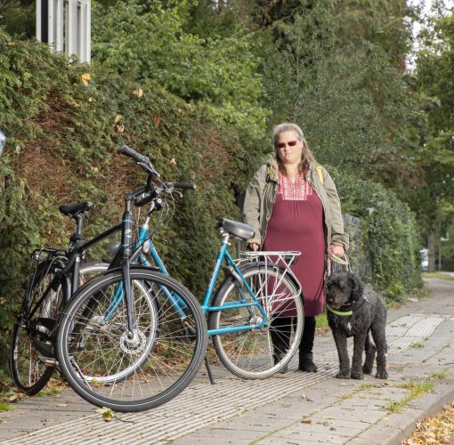 Een vrouw loopt met haar hulphond op de geleidelijn tegen twee geparkeerde fietsen aan